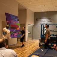Alisa Singer canvas from environmental graffiti collection being hung on uci wall